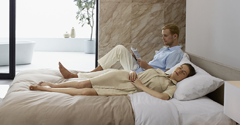 A man reading magazine  on the bed while a lady sleeping next to him