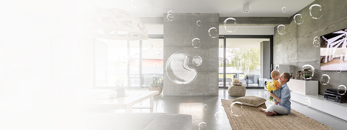 A mother hugging kid on the floor with bubble floating around in living room