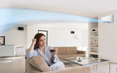 Lady drinking coffee with air flow from air condintioner flowing near the ceiling.